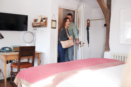 Couple Spending Romantic Weekend Away Opening Door Of Hotel Room