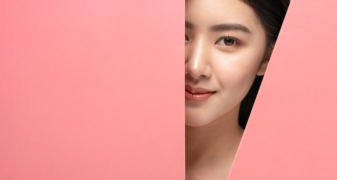 Beautiful young woman with clean fresh skin.Asian girl with beautiful brown bright eyes,expressive eyebrows looks into the hole of pink colored paper.Fashion,cosmetics,beauty,beauty salon,make-up.