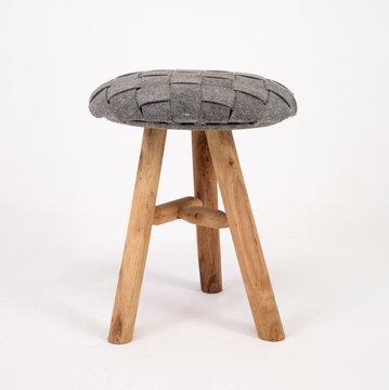 Old fashioned three legged wooden stool with grey cushion on white isolated background_2