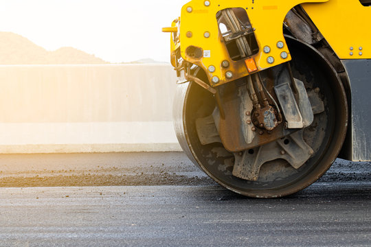 Asphalt road surface is smoothed with steel wheels, road construction machinery, asphalt paver