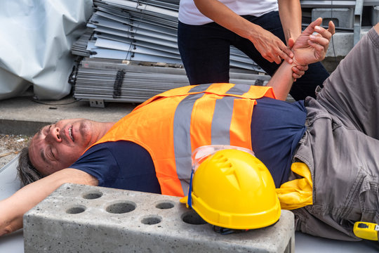 Cropped image of a paramedic's hands checking the pulse rate of a lying down construction worker injured at work