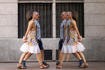 A couple are reflected in a glass wall as they walk beside CaixaForum cultural centre in Madrid
