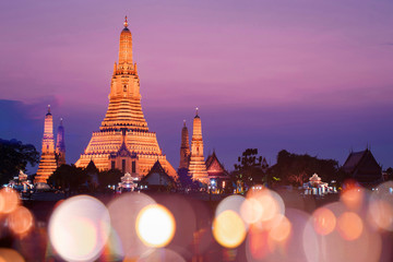 Tuinposter Bangkok Wat Arun temple with sunset and blur bokeh at foreground during sunset.