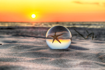 Beautiful sunset on the beach in Slowinski National Park near Leba, Poland. View of a starfish through a glass, crystal ball (lensball) for refraction photography. Wild, untouched nature.