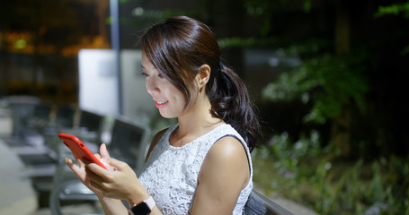 Wall Mural - Asian woman use of mobile phone in the park at night