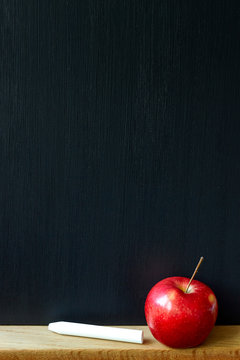 Back to school concept, close-up of a clean black chalk board, white chalk and red apple, selective focus, copy space