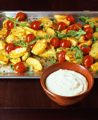 Baked potatoes with tomatoes and yoghurt-feta-dip on baking tray