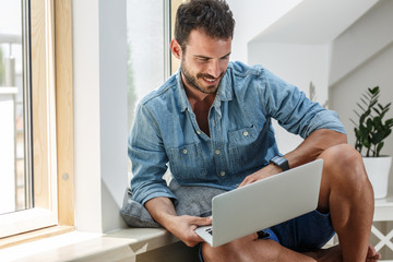 Handsome middle age man sitting in his apartment in living room by the window.He using laptop .