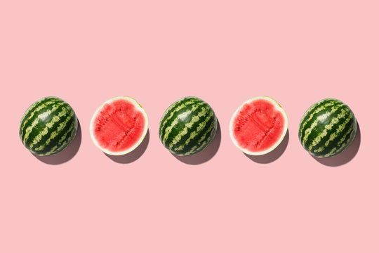 Row of fresh watermelon in center on pink backgrond. Top view