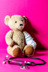 injured teddy bear with a bandage and stethoscope, pink background