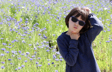 bored child scratching head having concerns over blooming floral field