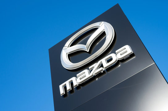 GUMMERSBACH, GERMANY - October 30, 2016: Mazda dealership sign against blue sky. Mazda is a Japanese automaker and produces over 1 million vehicles per year.