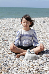 eyes closed child sitting for relaxation and mindfulness on beach