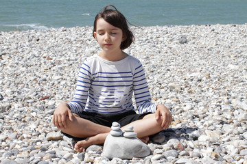 peaceful child sitting with pebbles for mindfulness and ocean energy