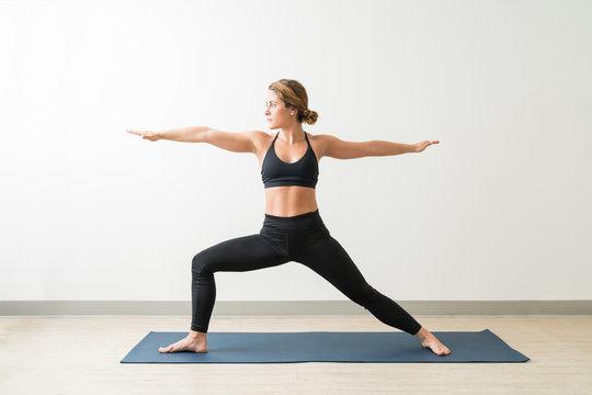 Caucasian Female Practicing Warrior Pose Ii In Yoga Studio