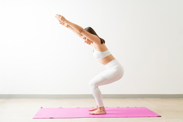 Beautiful Woman Practicing Chair Pose By Wall