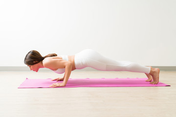 Side View Of Female Exercising Low Plank In Fitness Session