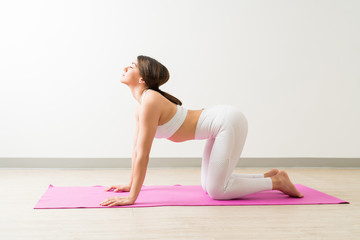Active Female Practicing Cow Pose In Yoga Studio