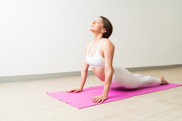 Woman Practicing Bhujangasana Yoga Pose By Wall