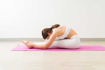 Side View Of Brunette Female Practicing Seated Forward Bend