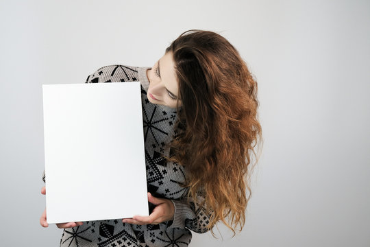 Girl and blank canvas. Young woman looking at mockup poster and standing over grey background.