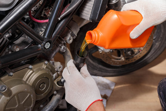 The process of pouring new oil into the motorcycle engine.