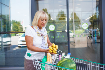 Senior woman at grocery shopping in front of the supermarket, she is puting bananas inside a cart filled with groceries