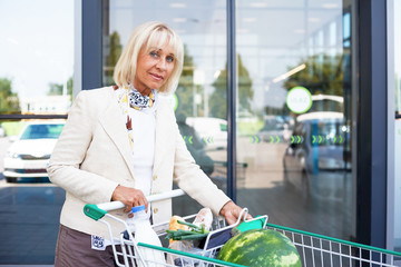 Senior woman doing grocery shopping at the supermarket. Mature elegant woman is pushing a cart filled with fruit, vegetables and other products