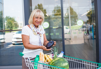Senior woman with a cart filled with groceries in front of the supermarket. Mature woman holding an eggplant above  a shopping cart.