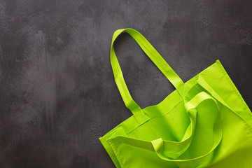 Plain green cotton reusable tote bag on rustic surface. Top view, blank space