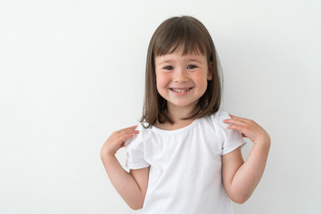 Joyful child in a white T-shirt on a light background. Cute girl smiles and does exercises.
