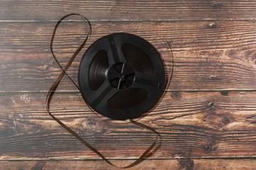 Vintage reel-to-reel audio recorder tape on wooden background
