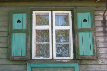 simple window with shutters on a green wooden wall