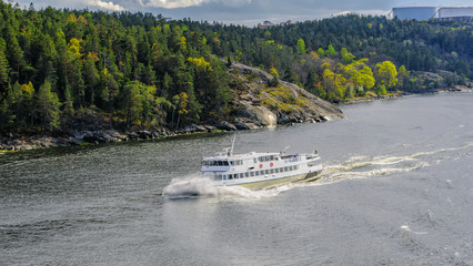 Commuter ferry cuts  through the waves in the Stockholm archipelago at a sunny spring evening.