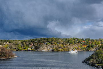Commuter ferry entering to Skurusundet strait in the Stockholm archipelago at a sunny spring evening.