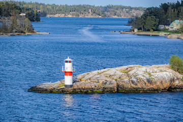 Beacon or small lighthouse in red and white at a rocky shore of Oxdjupet strait during the evening with coniferous forest and dwelling islands on the background.