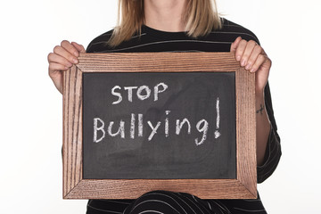 cropped view of girl holding chalkboard in wooden frame with stop bullying lettering isolated on...