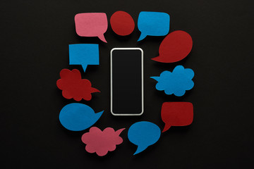 top view of smartphone with blank screen on black background with empty speech bubbles,...