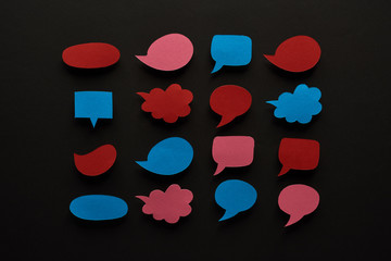 top view of empty speech bubbles on black background, cyberbullying concept