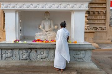 Woman placing flower offerings to Buddha, Anuradhapura, Sri Lanka