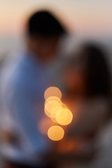 Silhouette of a young couple kissing on the seashore at sunset. Blurred background.