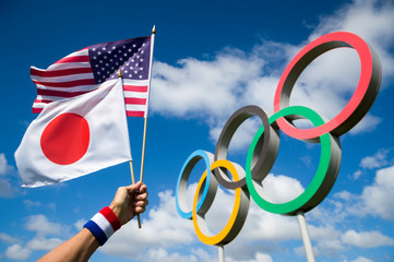 LONDON - APRIL 19, 2019: Hand wearing red white and blue wristband holds Japanese and American flags together in front of a large set of shiny metallic Olympic Rings under bright blue sky.