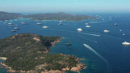 Fototapete - View from above, stunning aerial view of the beautiful Cala Di Volpe bay full of boats and luxury yachts. A turquoise sea bathes the green and rocky coasts. Emerald Coast, Sardinia, Italy.