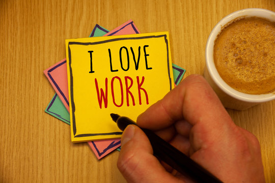 Text sign showing I Love Work. Conceptual photo To be happy satisfied with job Be doing what you most likeMan creating yellow pink blue papers Hand holding black pen cup of coffee