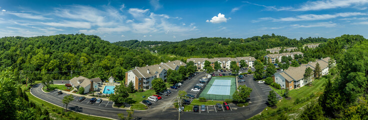 Aerial view of typical American midwest middle class apartment complex with club house, pool, tennis court and parking lot