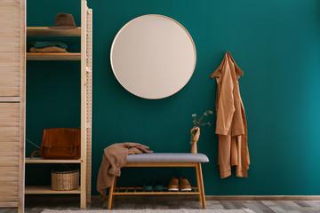 Round mirror on green wall in stylish hallway interior