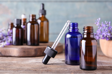 Bottles of lavender essential oil and flowers on wooden table against blue background
