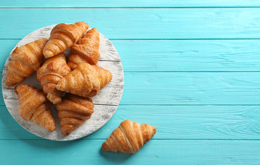 In de dag Brood Board with tasty croissants and space for text on light blue background, flat lay. French pastry