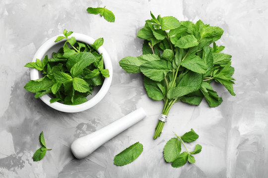 Fresh mint with mortar and pestle on grey marble table, flat lay