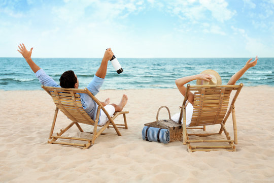 Happy young couple with wine sitting on deck chairs at sea beach
